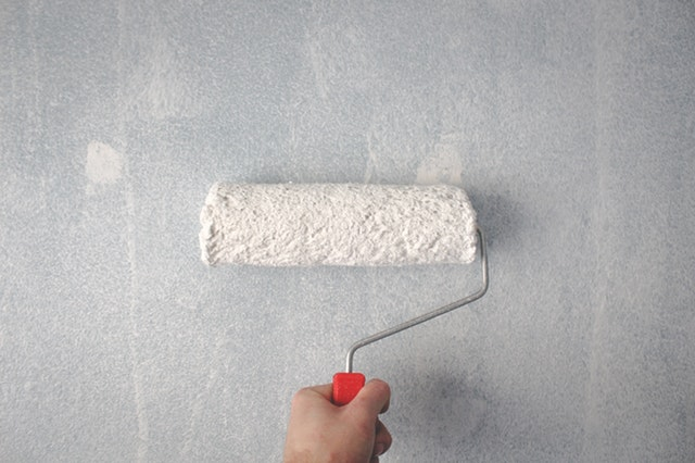 person-holding-paint-roller-on-wall-1669754.jpg